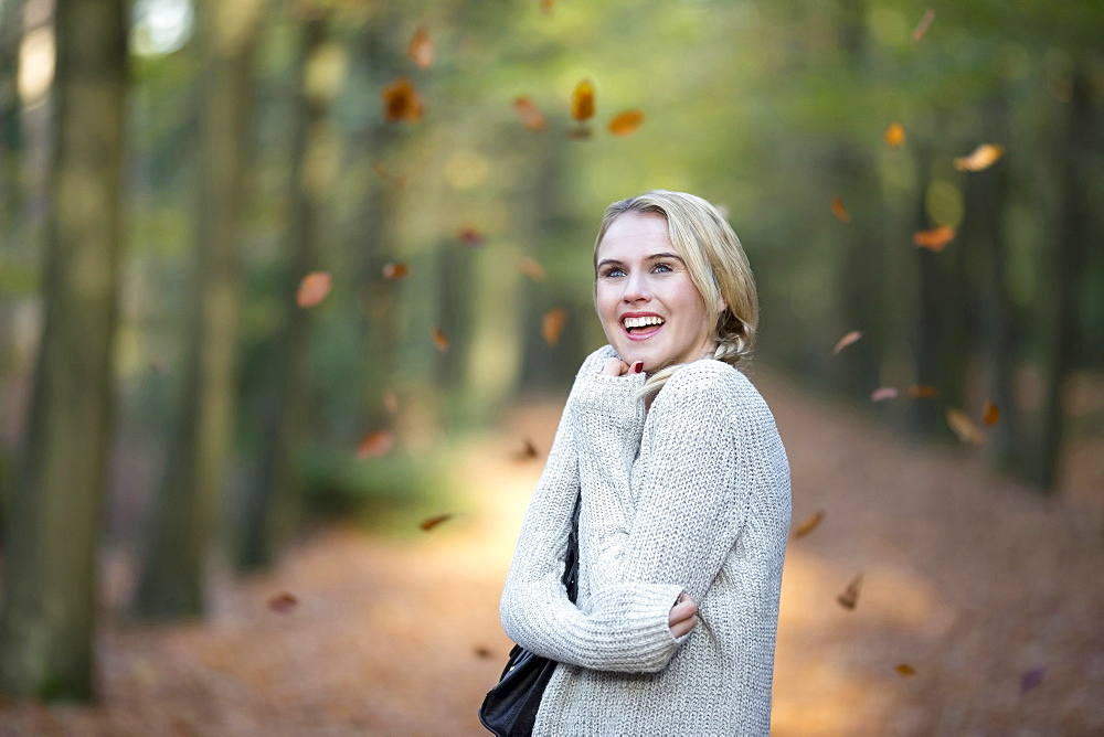 Portrait of smiling woman while leaves falling