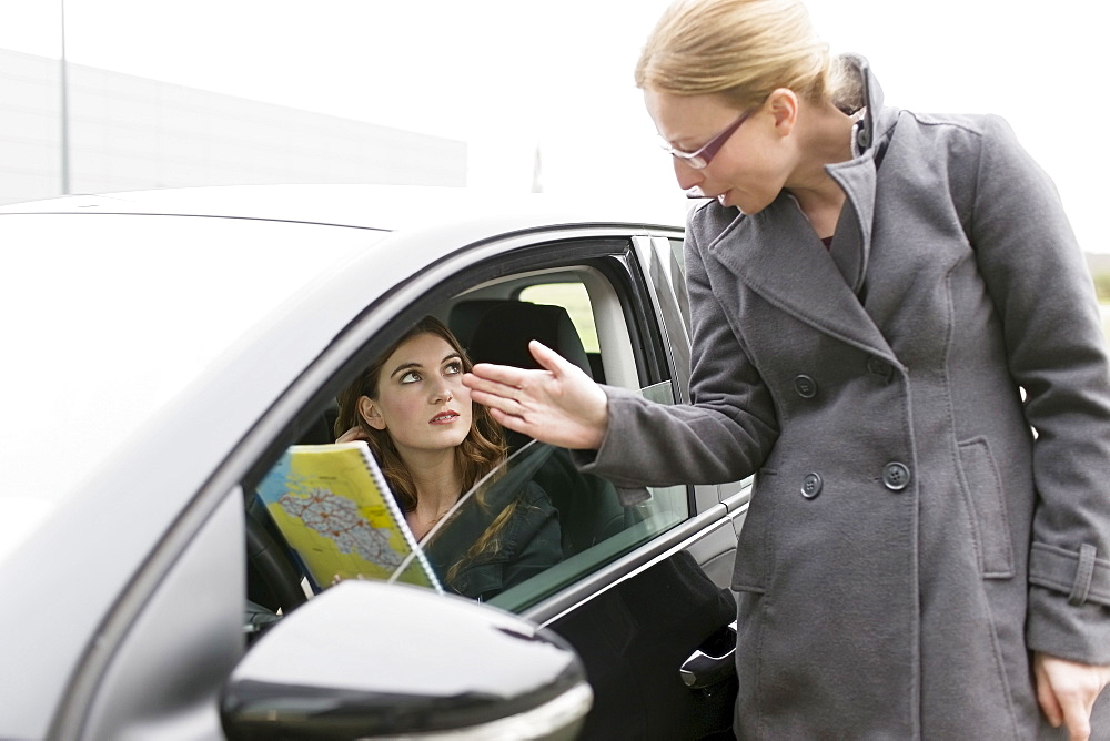 Woman giving directions to young woman in car