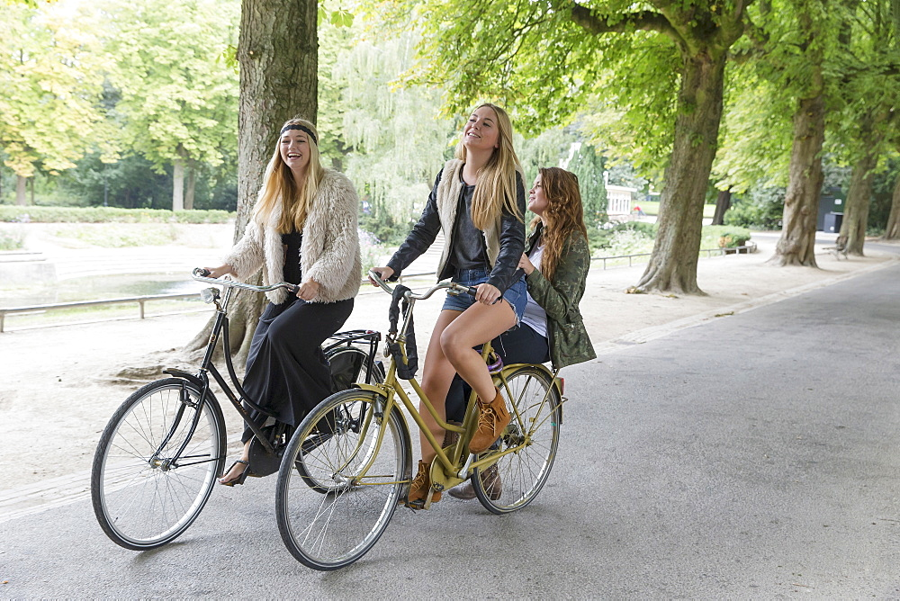 Female friends riding bike in park, Netherlands, Groningen