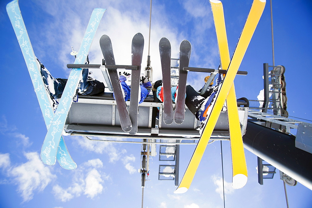 Family of skiers on ski lift seen from below