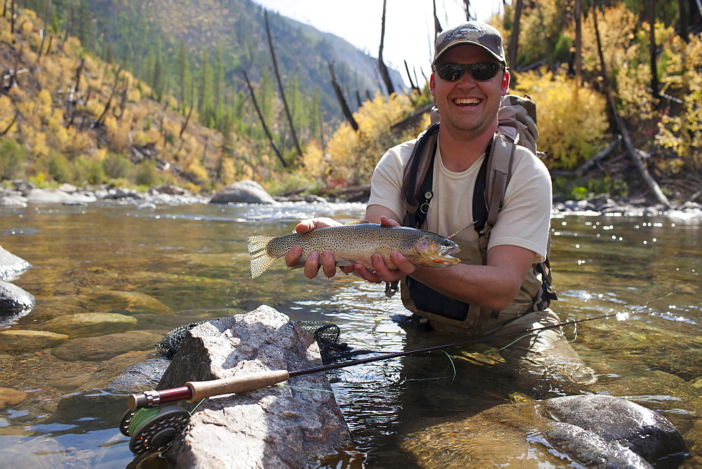 Fisherman showing fresh trout, North Fork Blackfoot River, Montana, USA