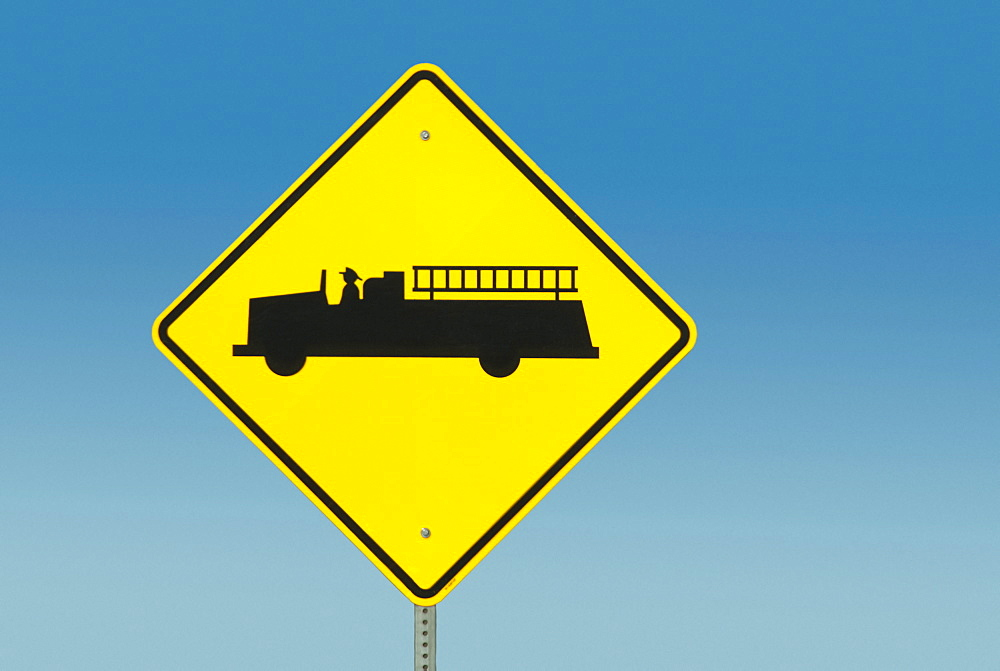 Yellow road sign depicting fire truck
