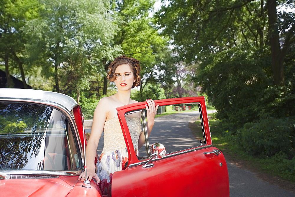 Portrait of elegant woman next to vintage car, Goirle