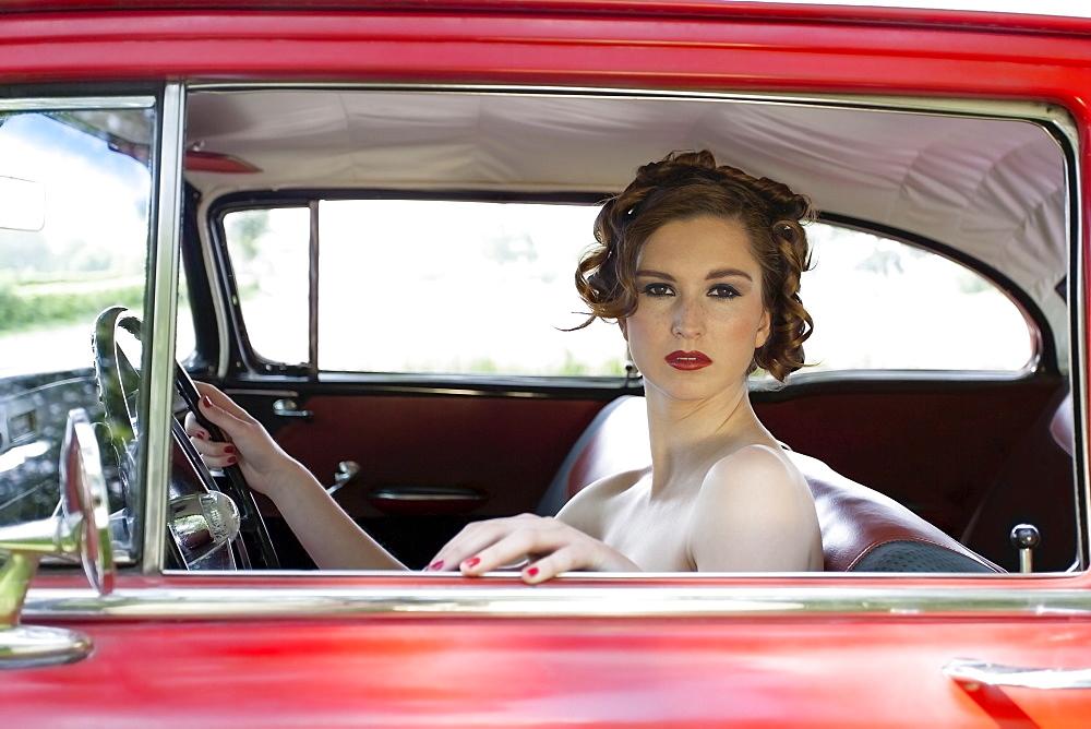 Portrait of elegant woman in vintage car