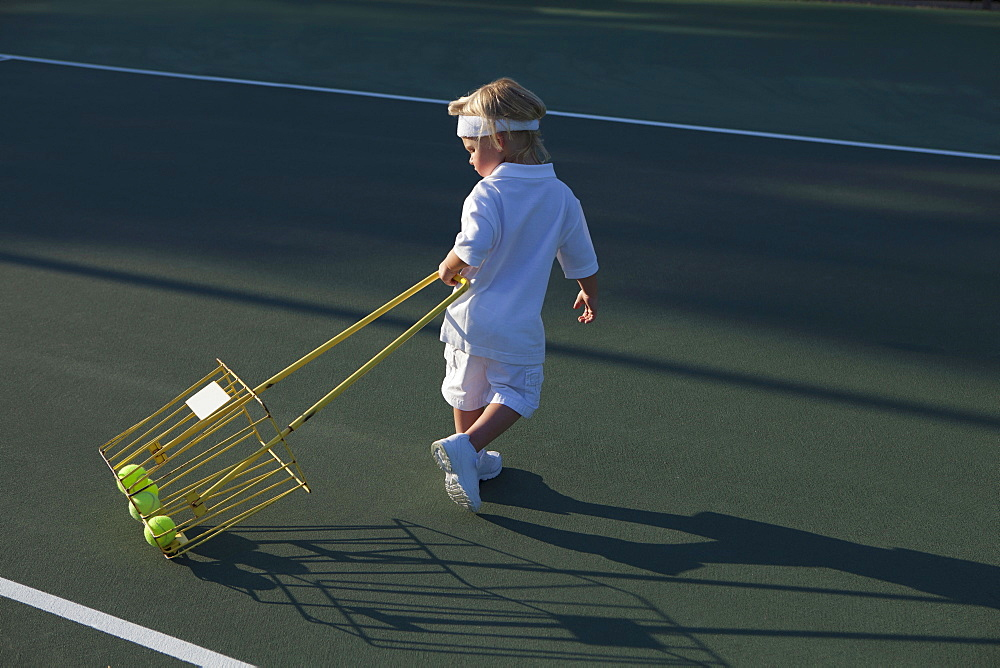 Boy (2-3) pulling basket with tennis balls