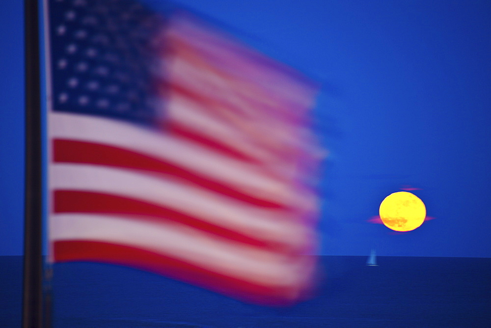 US flag and rising moon over Lake Michigan