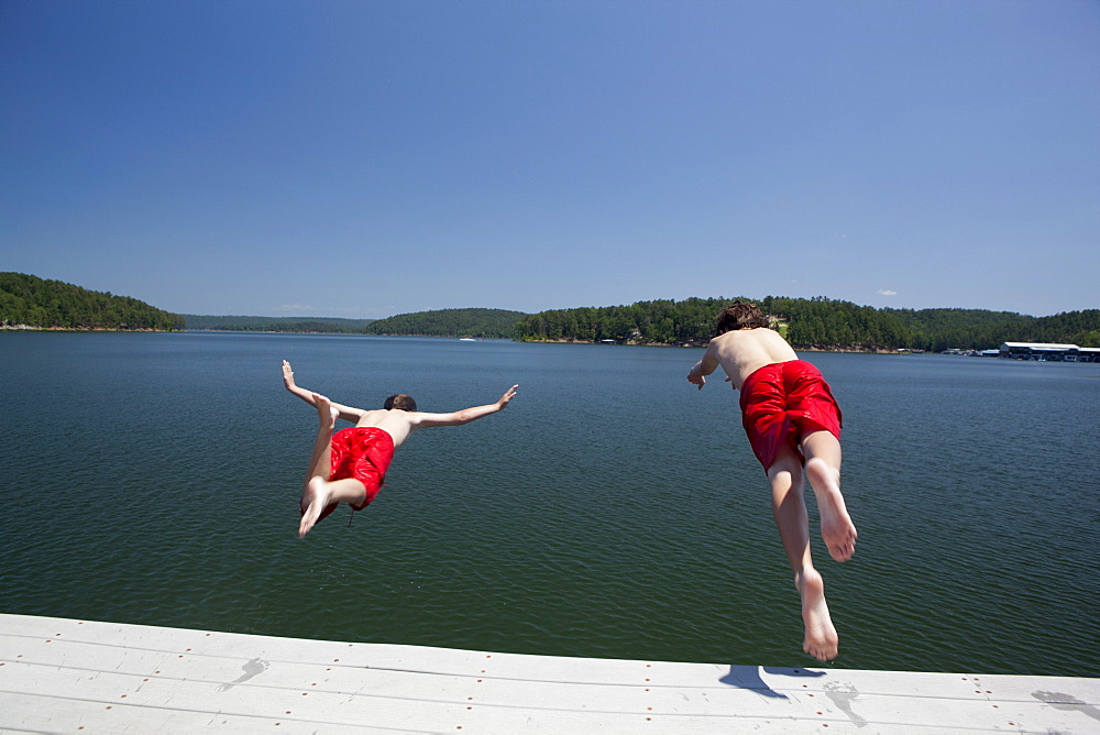 USA, Arkansas, Murfreesboro, Two brothers (8-9, 12-13) jumping into water, USA, Arkansas, Murfreesboro