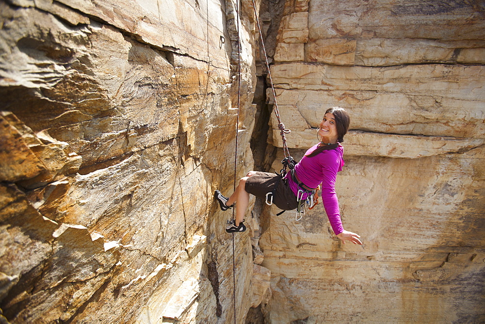 Smiling woman rock climbing