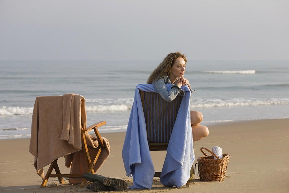 France, Pas-de-Calais, Escalles, Young women sitting on chair on empty beach, France, Pas-de-Calais, Escalles
