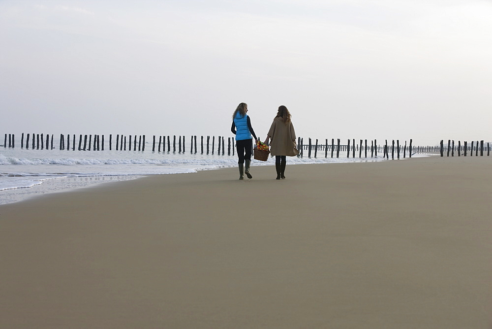 France, Pas-de-Calais, Escalles, Two women strolling on empty beach, France, Pas-de-Calais, Escalles
