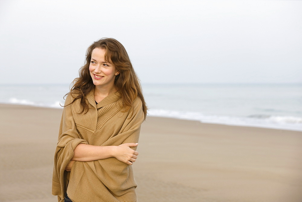 Young woman strolling on empty beach