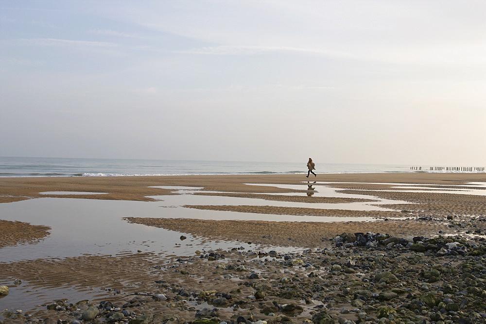 France, Pas-de-Calais, Escalles, Young woman on empty beach, France, Pas-de-Calais, Escalles
