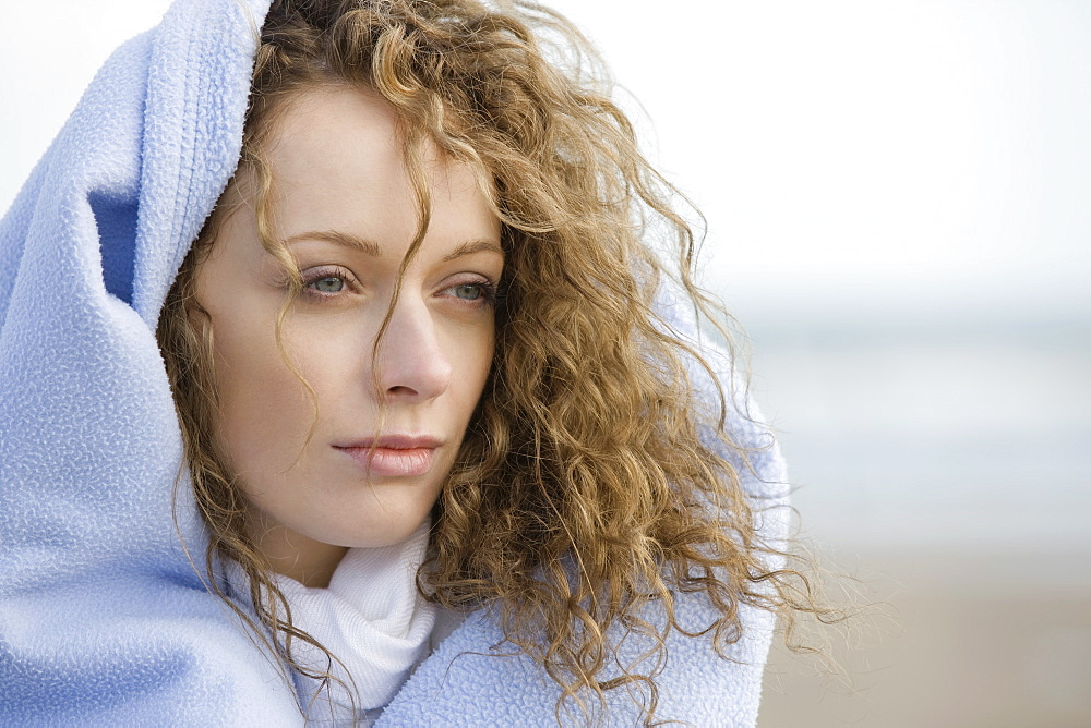 Portrait of young woman wrapped in blanket