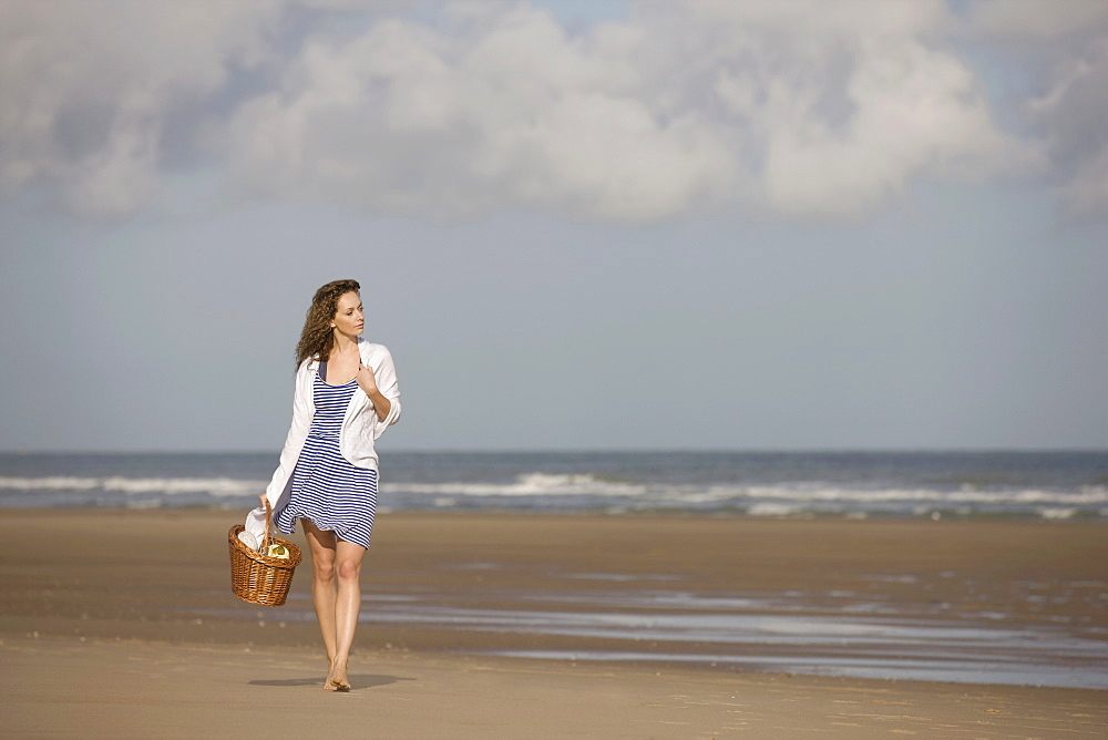 France, Pas-de-Calais, Escalles, Young woman strolling on empty beach, France, Pas-de-Calais, Escalles