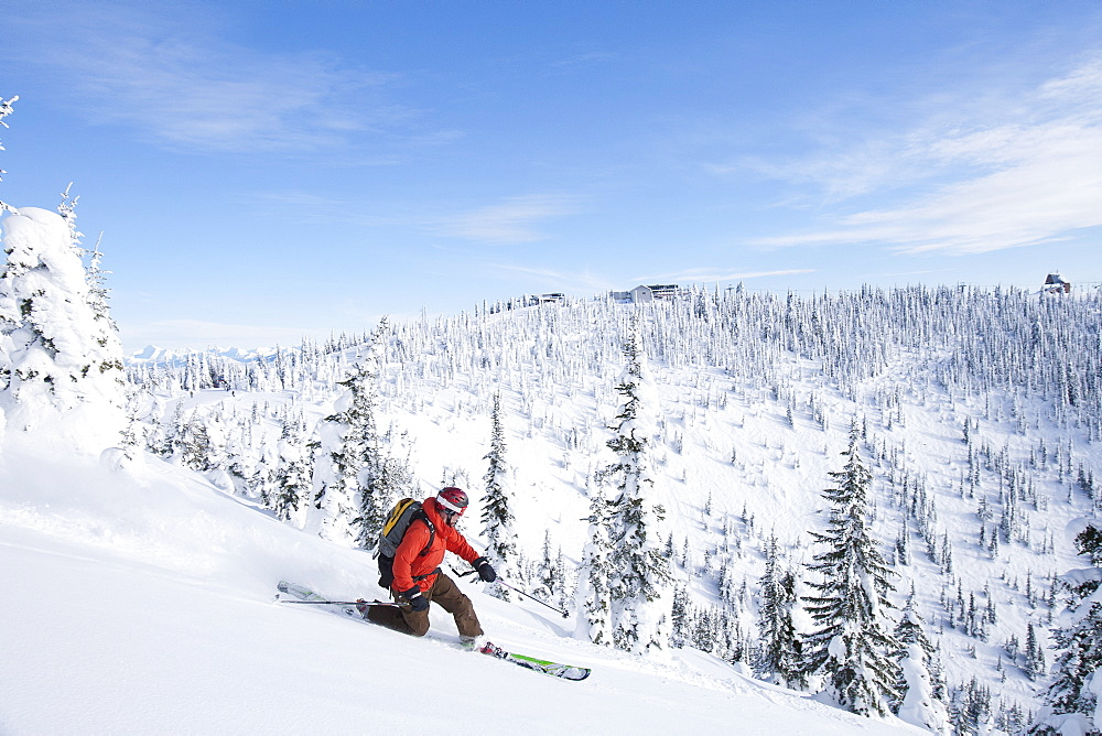 Man skiing powder in mountain scenery