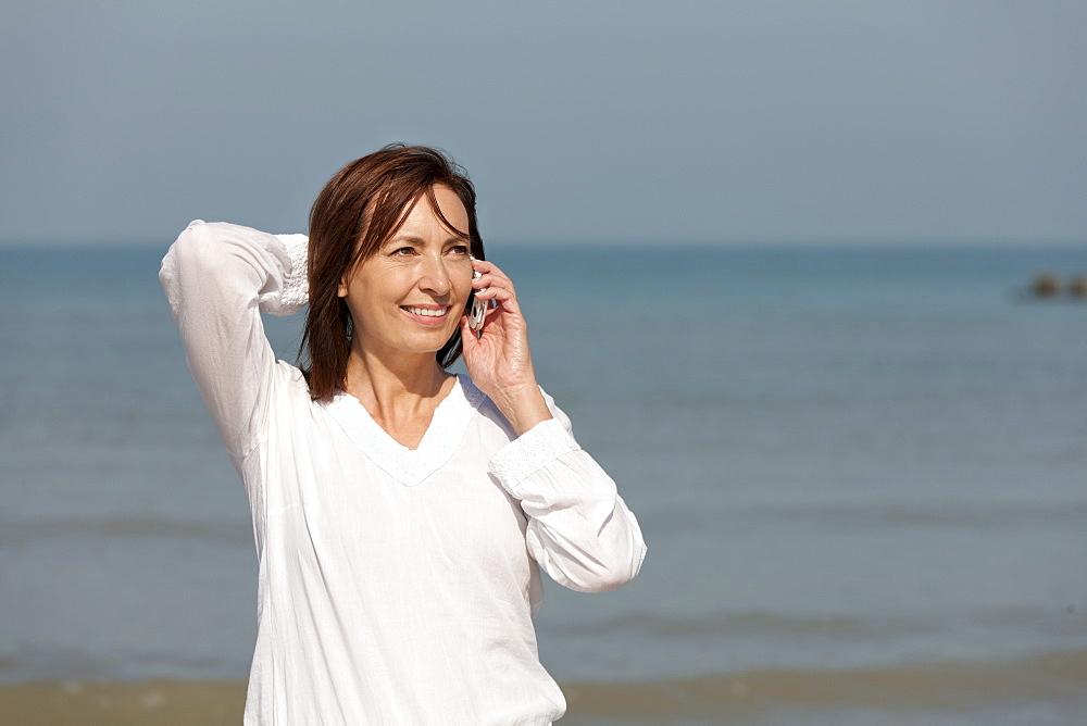 Woman on beach talking on phone