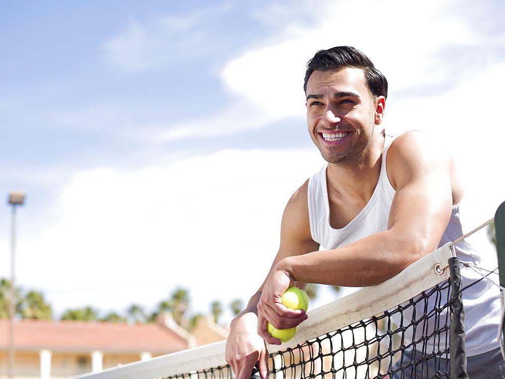 Smiling man standing near tennis net