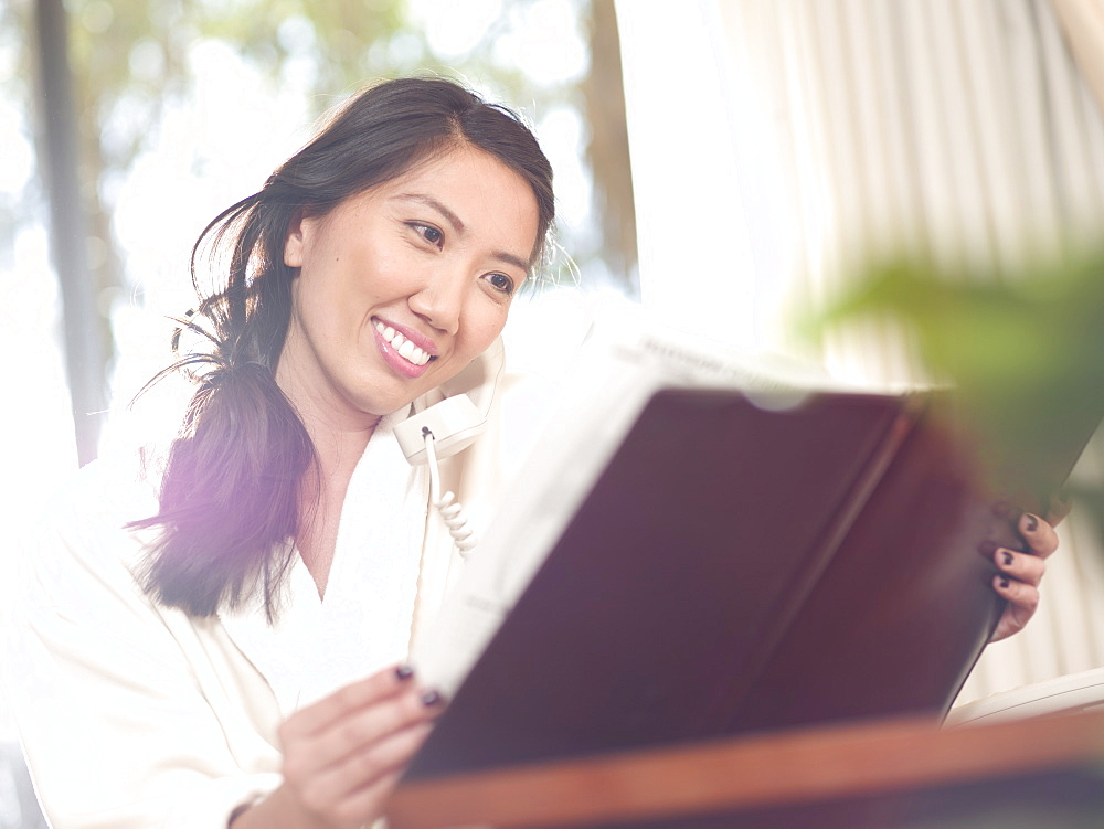 Woman ordering room service in hotel