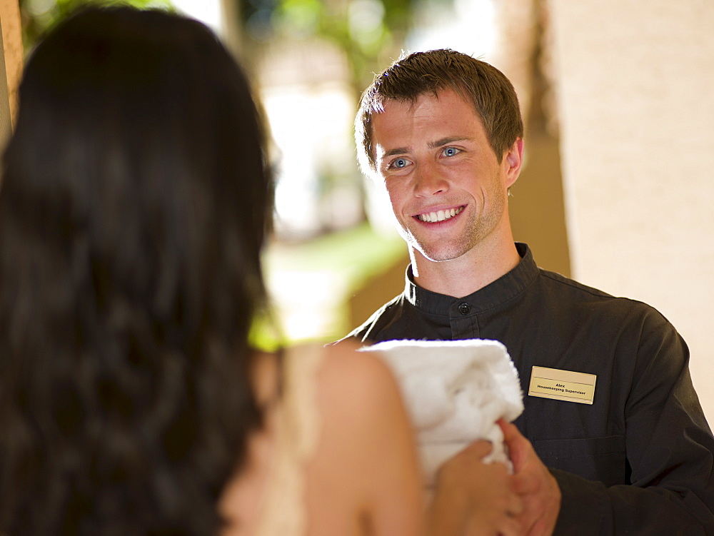 Man from room service delivering towels to hotel guest