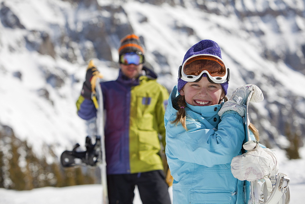 USA, Colorado, Telluride, Father and daughter (10-11) posing with snowboards in mountain scenery