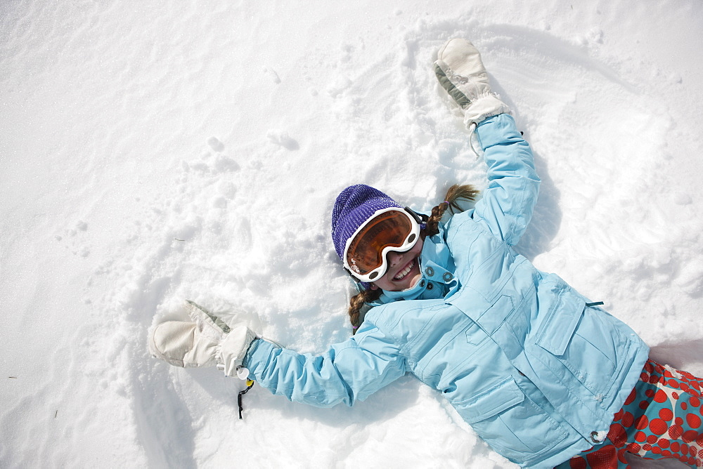 Girl (10-11) in ski gear doing snow angel