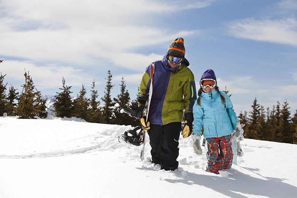 USA, Colorado, Telluride, Father and daughter (10-11) posing with snowboards in winter scenery