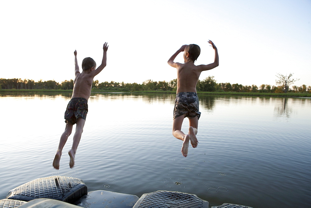 USA, Texas, Texarkana, Two boys (8-9) jumping into lake