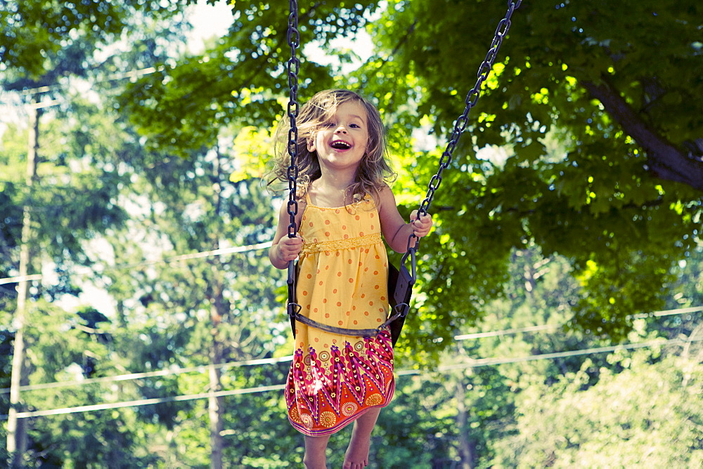 Girl (2-3) on swing in playground