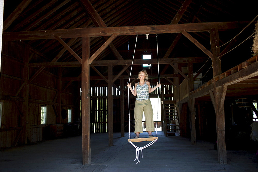 USA, Vermont, Dorset, Woman on swing in barn