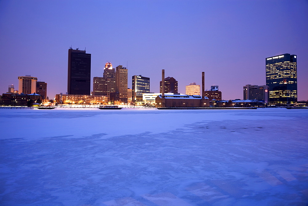 USA, Ohio, Toledo skyline across frozen river, dusk