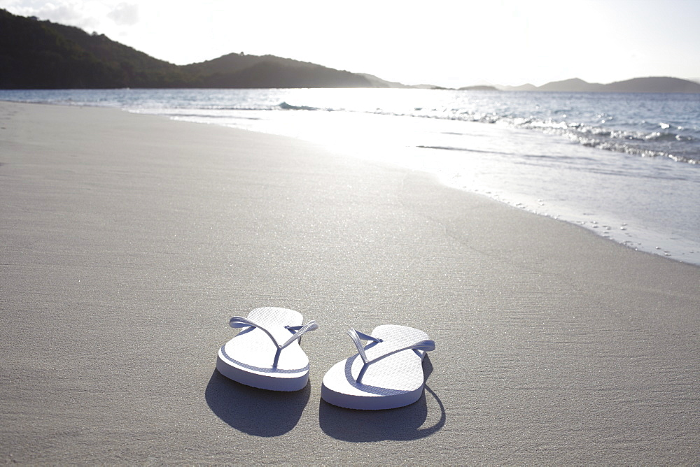 United States Virgin Islands, St. John, Pair of flip flops left on empty beach, United States Virgin Islands, St. John