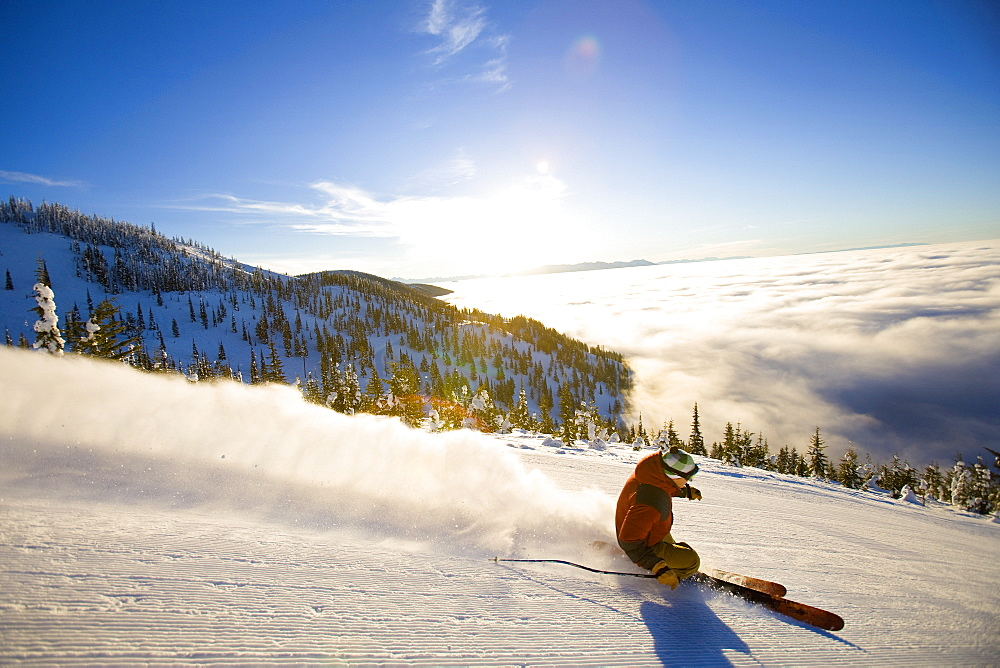 USA, Montana, Whitefish, Male skier on mountain slope at sunrise