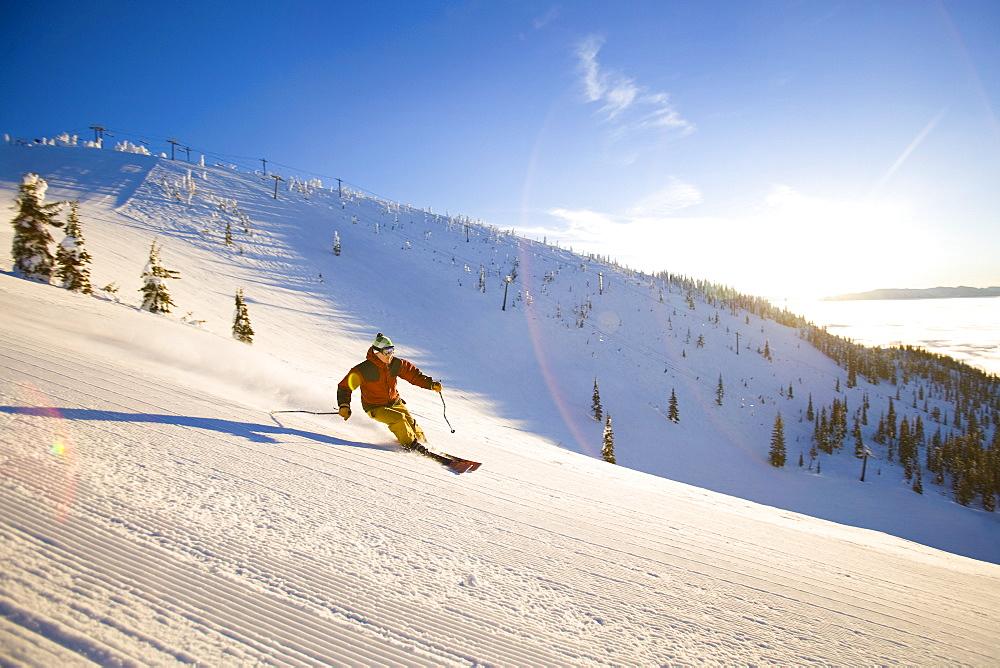 USA, Montana, Whitefish, Male skier on mountain slope at sunrise
