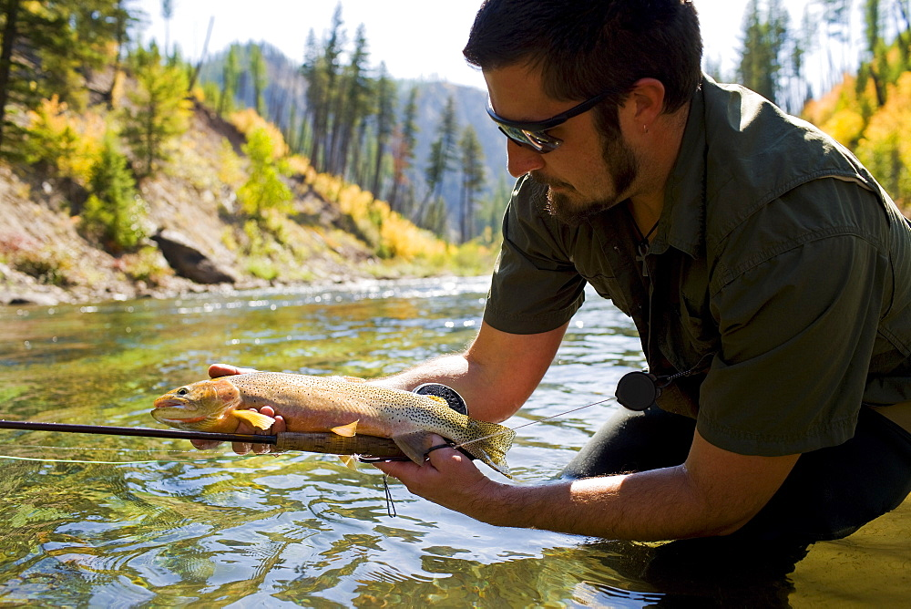 USA, Montana, Man holding fish in North Fork of Blackfoot River