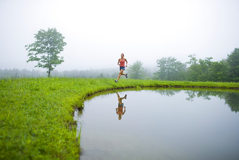 USA, Vermont, Landgrove, Woman jogging by lake