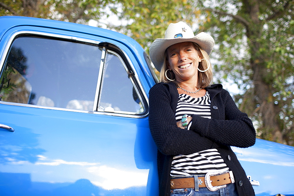 USA, Colorado, Carbondale, Portrait of cowgirl with old fashioned pickup truck