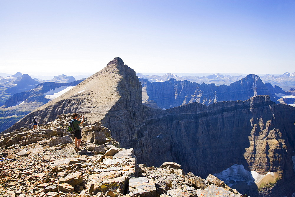 USA, Montana, Glacier National Park, Hikers taking pictures at top of Mt Siyeah