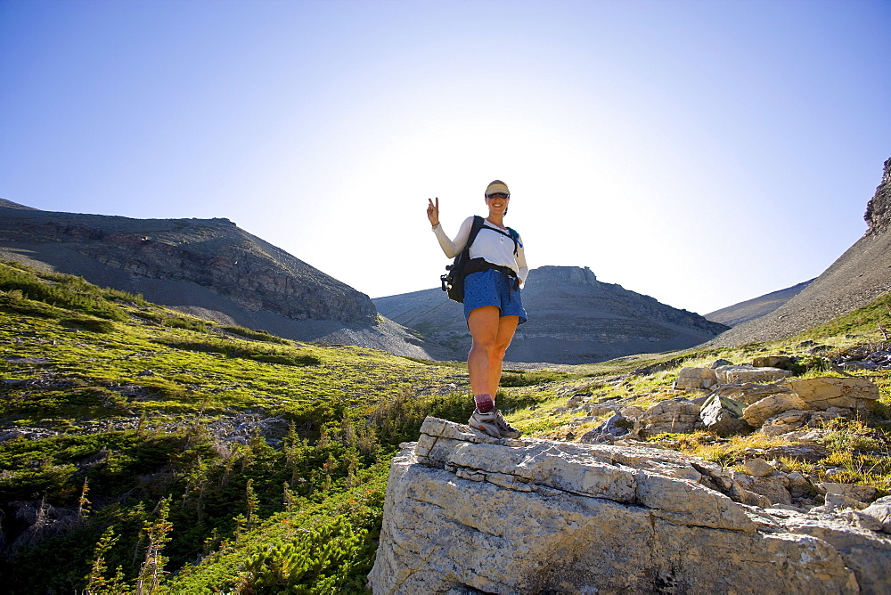 USA, Montana, Glacier National Park, Young woman posing with peace sign