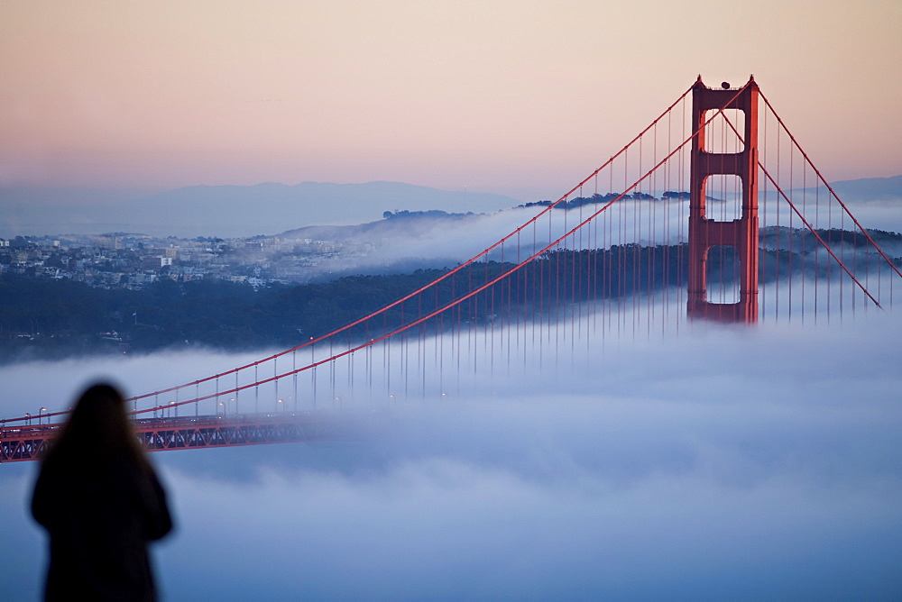 USA, California, San Francisco, Woman watching Golden gate Bridge in fog