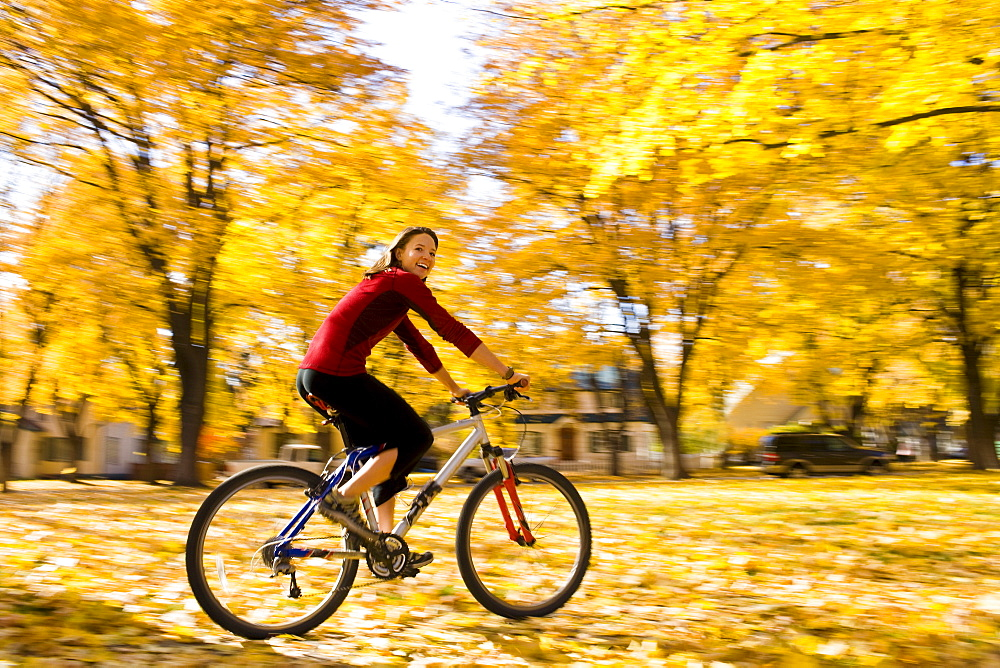 USA, Montana, Kalispell, Young woman cycling in park