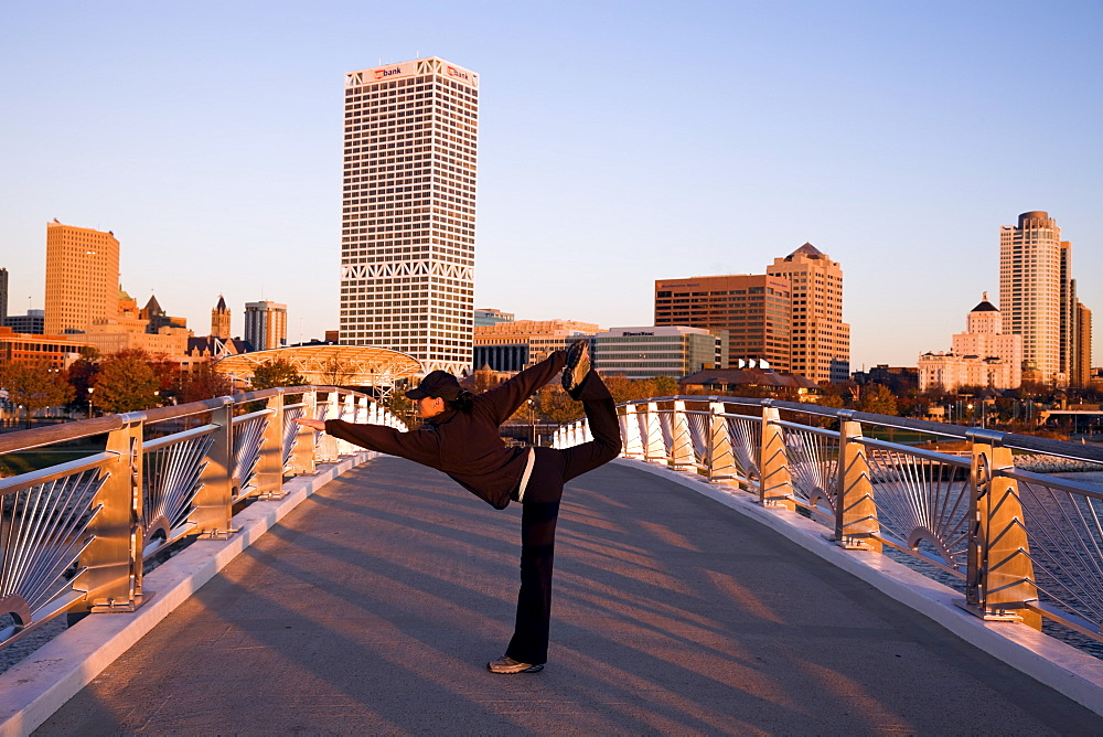 USA, Wisconsin, Milwaukee, Woman doing yoga on bridge in city