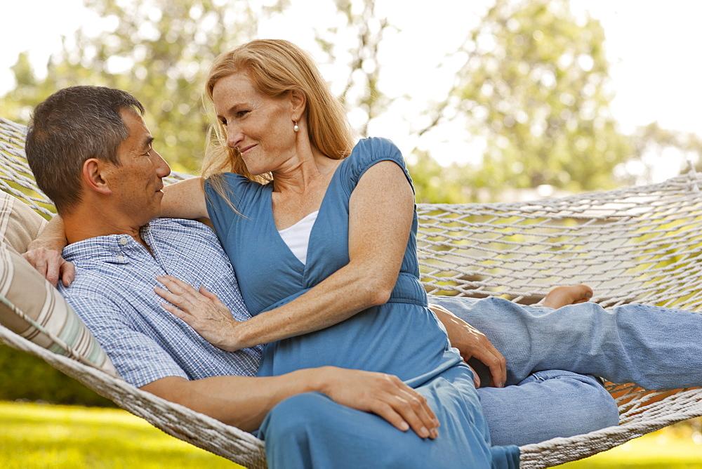 USA, Utah, Provo, Smiling mature couple relaxing in hammock in garden