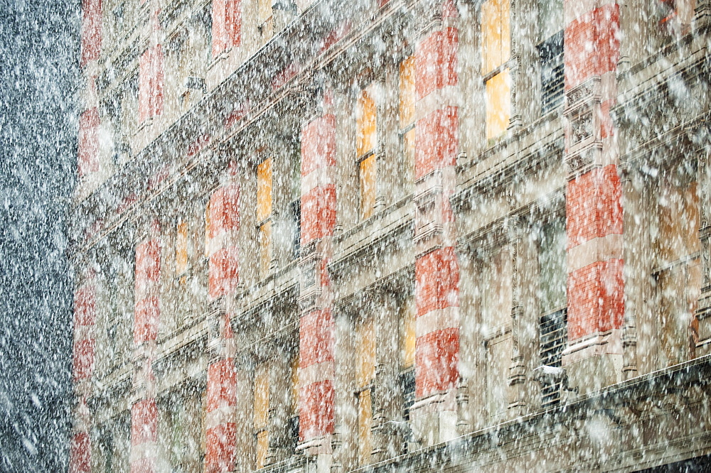 Snow falling in front of apartment building