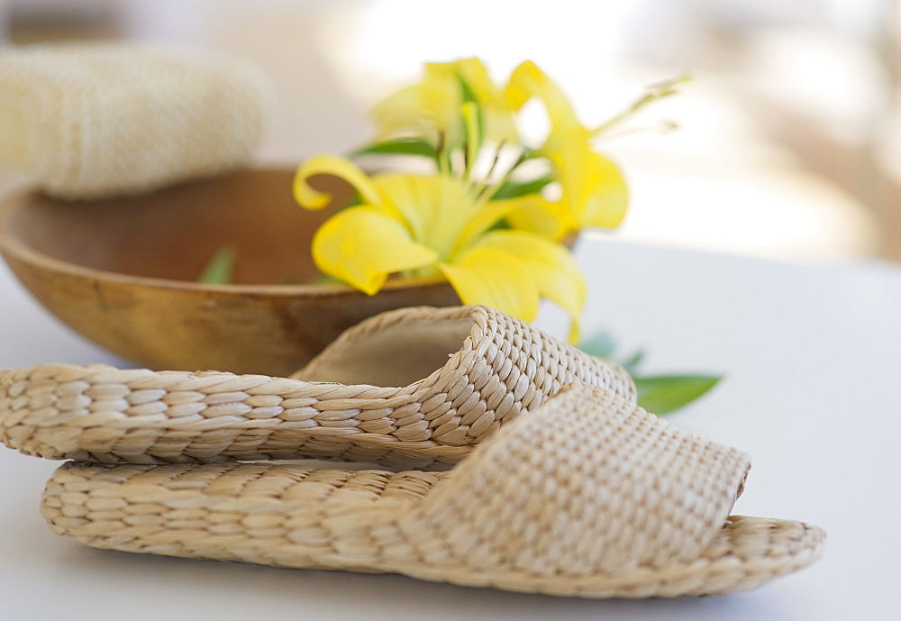 Slippers beside a wooden bowl with yellow lilies in it