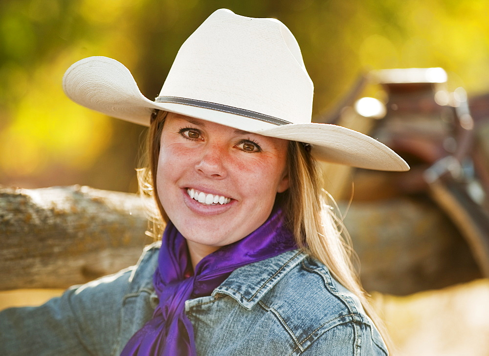 Cowgirl beside fence