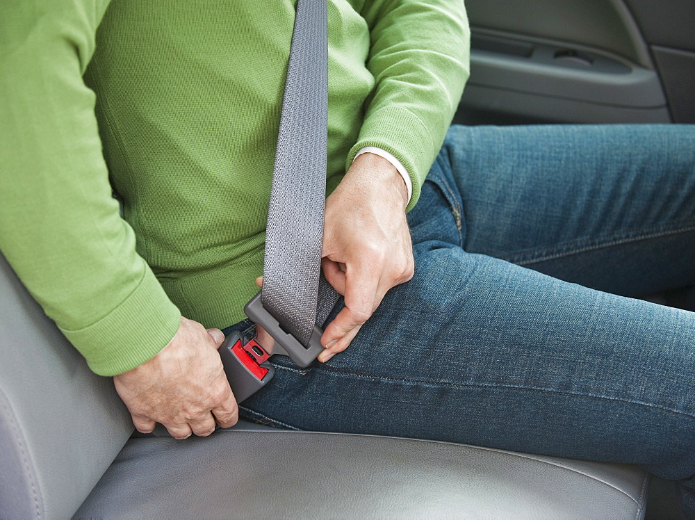 Man buckling seat belt in car