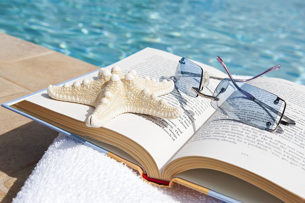 Book and sunglasses by swimming pool