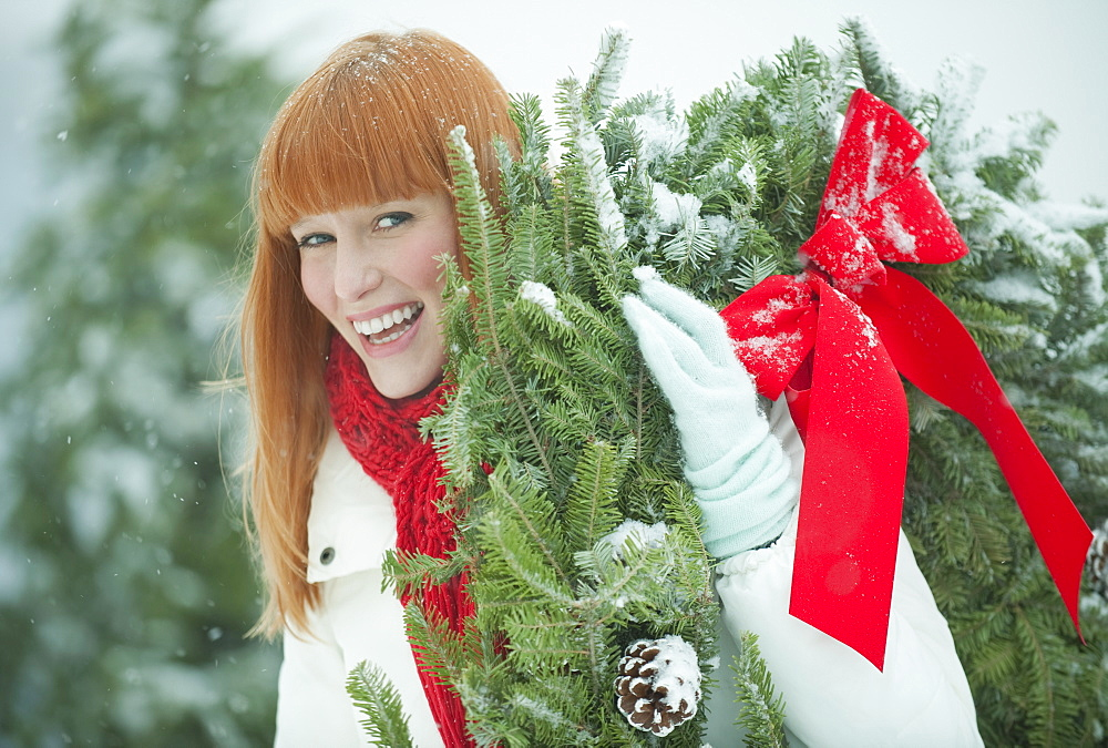Woman carrying Christmas wreath