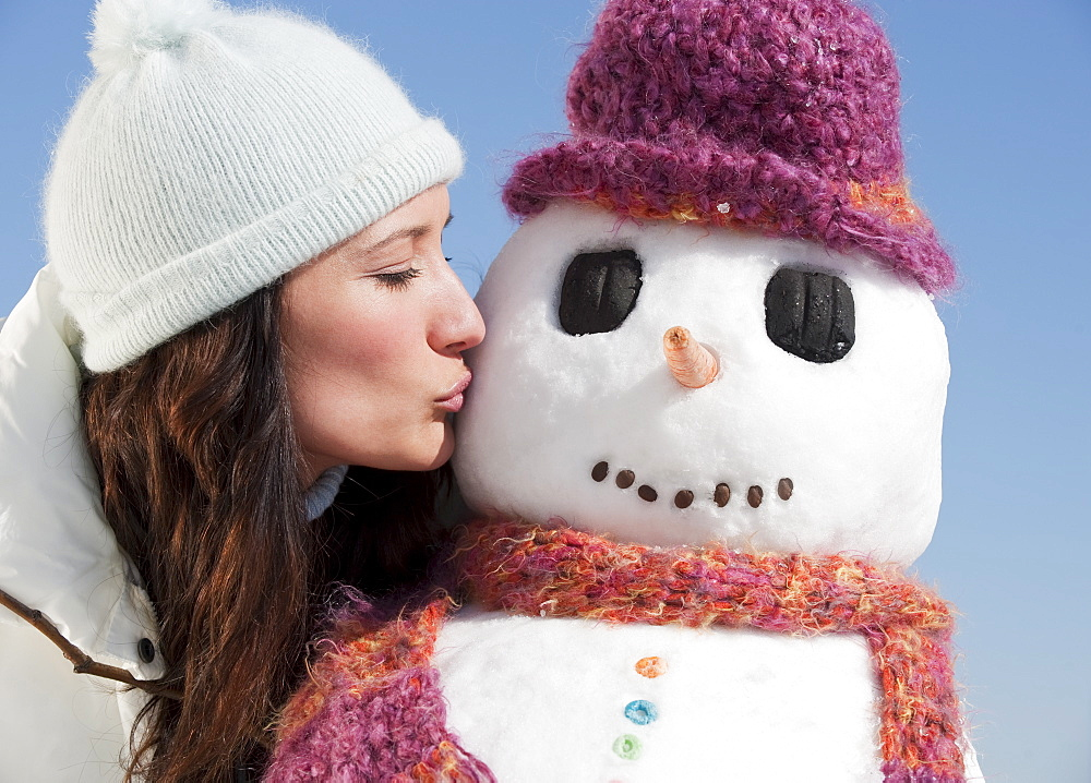 Woman kissing snowman