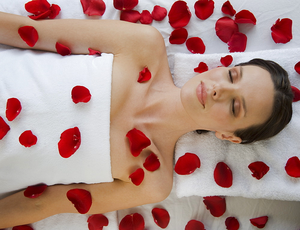 Woman covered in flower petals laying on massage table